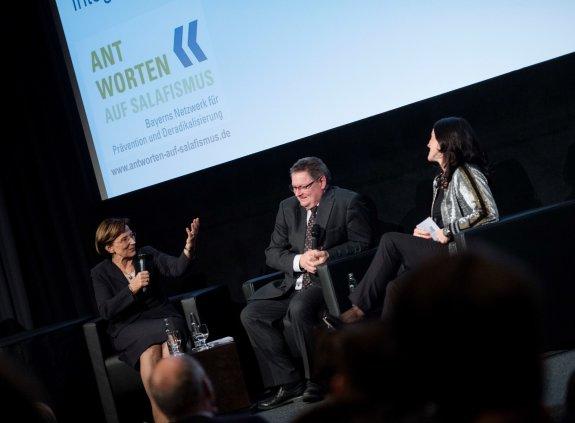 Staatsministerin Emilia MÜller, Staatssekretär Gerhard Eck und Moderatorin Melitta Varlam sitzen auf der Bühne und sprechen miteinander