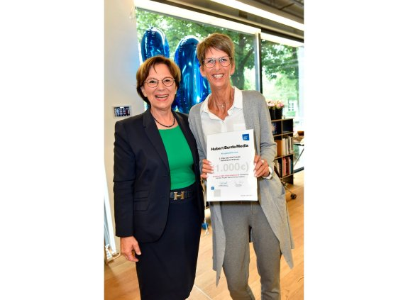 Staatsministerin Emilia Müller mit Preisträgerin, die eine Urkunde in die Kamera hält