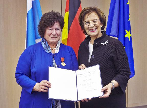 Brigitte Trummer und Staatsministerin Emilia Müller halten eine Urkunde in die Kamera