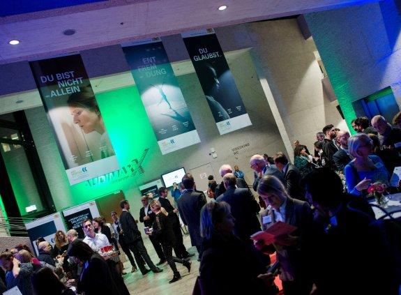 Foyer der Filmhochschule, von der Decke hängen Filmplakate, darunter stehen Gäste