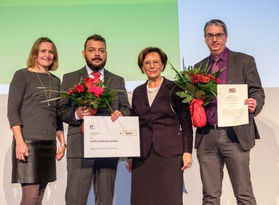 Staatsministerin Emilia Müller mit einer Mitarbeiterin und zwei Mitarbeitern des Gewinnerunternehmens, die Urkunden und Blumen halten, auf der Bühne