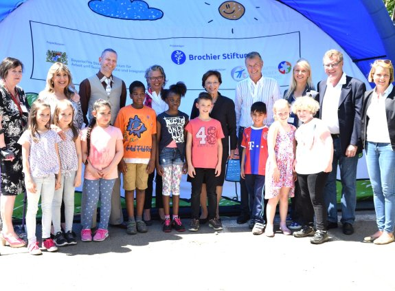 Gruppenbild mit Emilia Müller, links und rechts neben ihr stehen weitere Erwachsene, vor ihr stehen Kinder