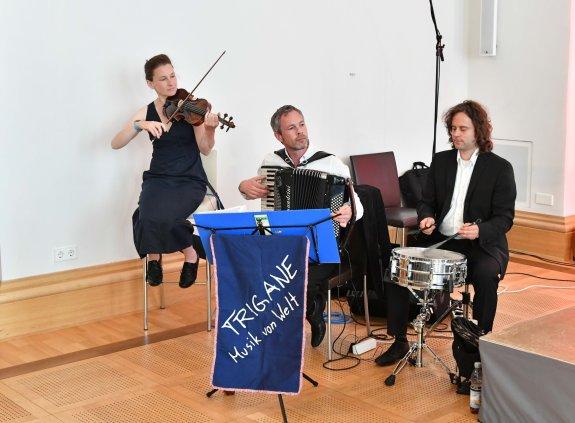 Musiktrio mit Violinistin, Akkordeonspieler und Schlagzeuger musizieren