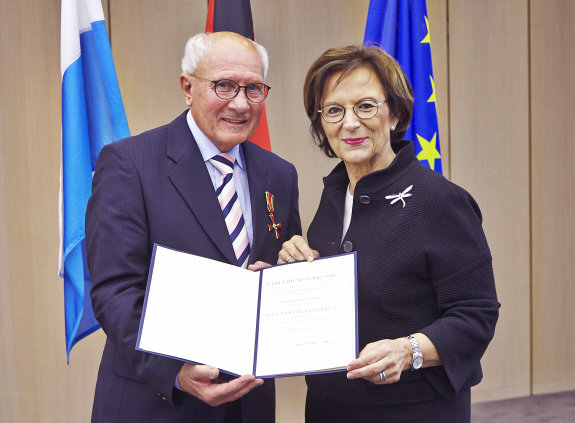 Friedrich Sommer und Staatsministerin Emilia Müller halten eine Urkunde in die Kamera