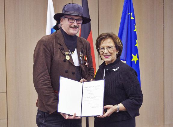 Helmut Kindl und Staatsministerin Emilia Müller halten eine Urkunde in die Kamera