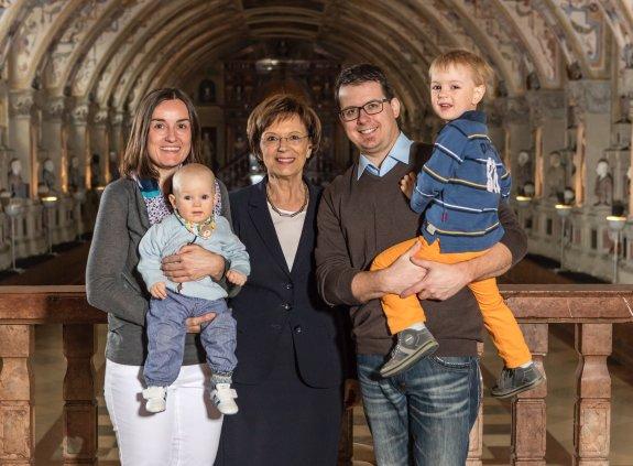 Staatsministerin Emilia Müller mit dem Gewinner der diesjährigen Osterverlosung und dessen Familie in der Residenz München.